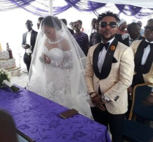 Oritsefemi standing next to his bride at their wedding -dilyfamily.ng